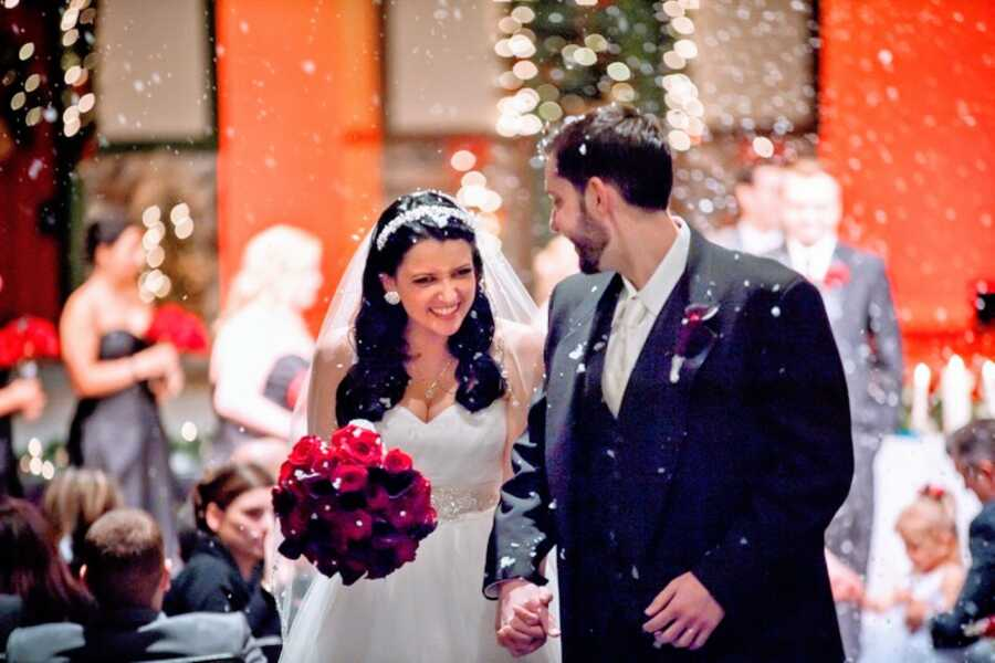 Newlywed couple smile big as they walk down the aisle together with fake snow coming down