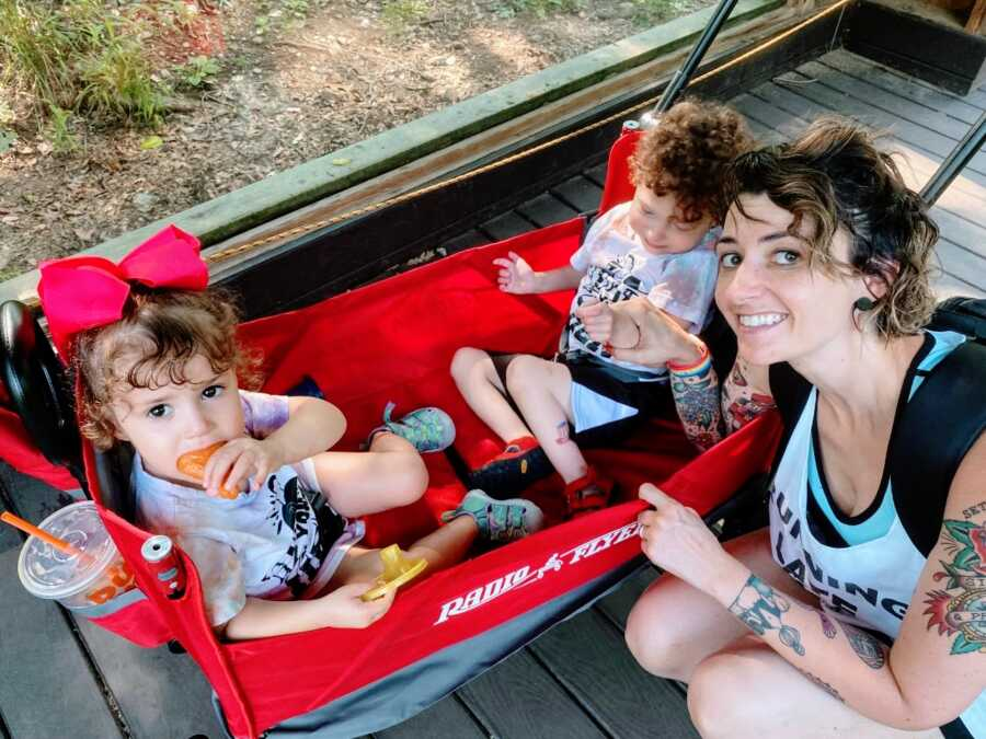 Solo mom takes a photo with her two kids in a red Radio Flyer wagon while at the zoo