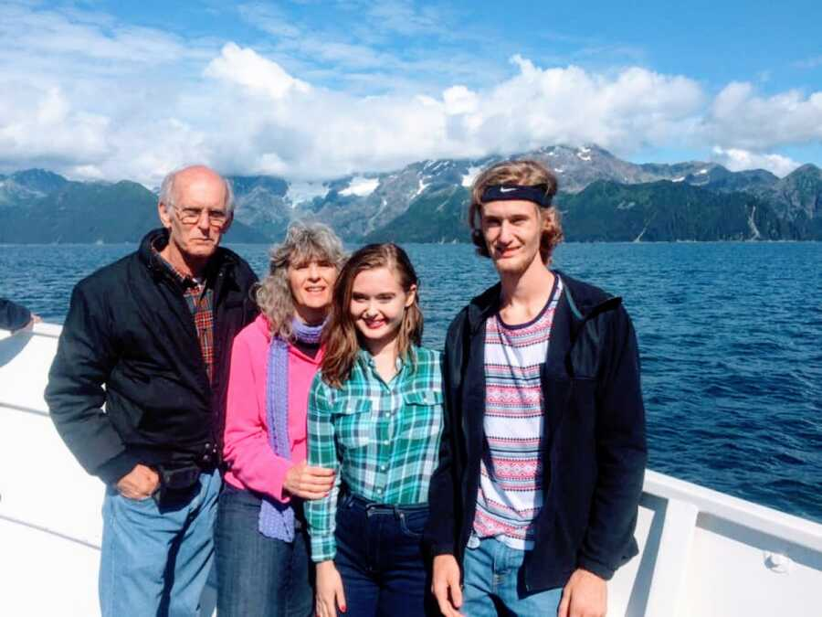 Young girl in green plaid shirt poses with her family on a boat with a mountain scene behind them
