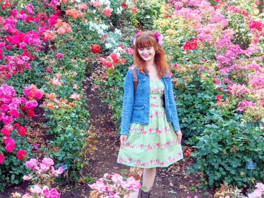 Young woman accepting her autistic identity poses in front of a ton of flowers in a floral dress with matching flowers in her hair