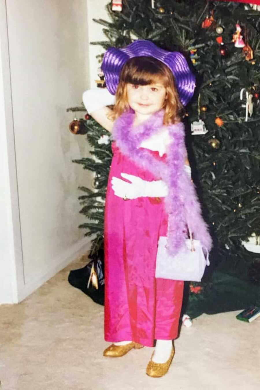Little girl dressed in a pink dress with a purple hat, feather boa, purse, and white gloves poses in front of a Christmas tree