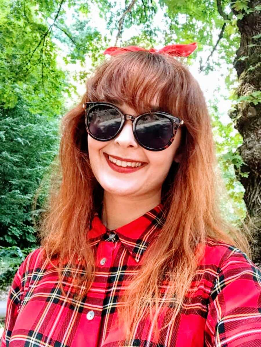 Young woman with autism and ADHD takes a selfie in a red plaid shirt with sunglasses on and a red bow in her hair