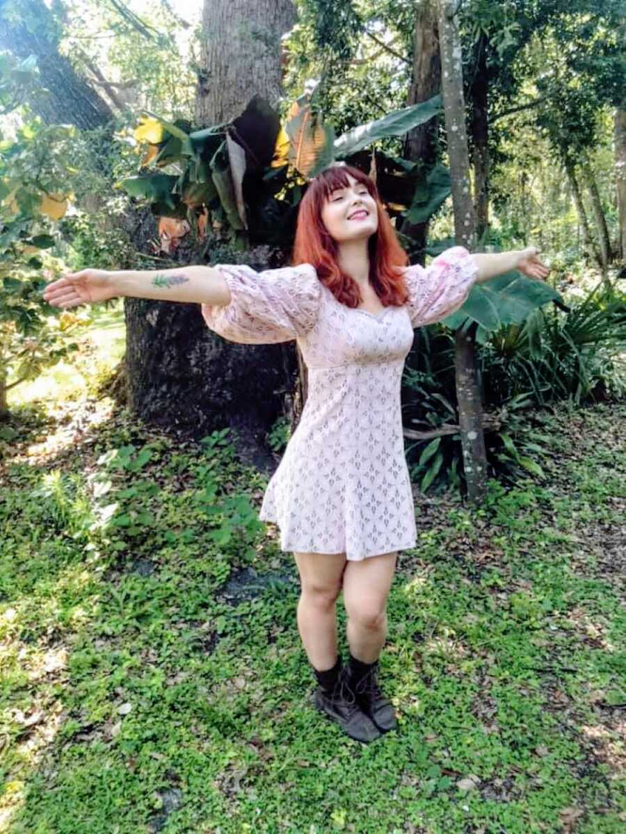 Young woman embraces her autistic identity and the nature around her while on a walk in boots and a dress