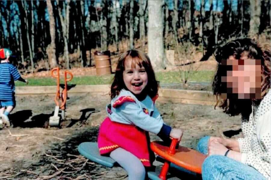 Young girl rides on a seesaw with her narcissistic mother at the playground