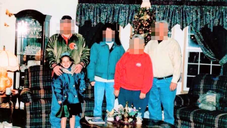 Young girl experiencing sexual abuse from her father poses with her family in front of the Christmas tree with a green dress on