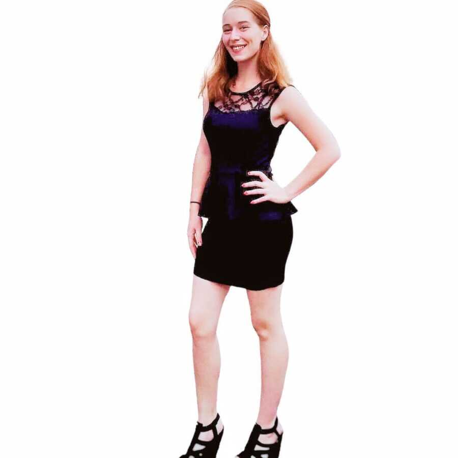 Woman recovering from a drug addiction and childhood trauma poses in a black dress and heels