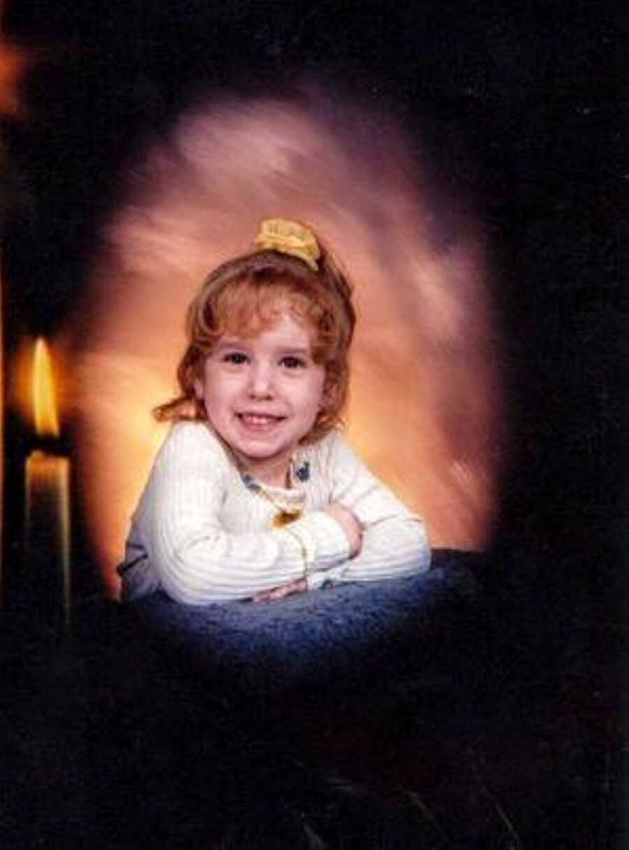 Little girl experience sexual abuse at home smiles for a photo with a sunset backdrop and a candle next to her