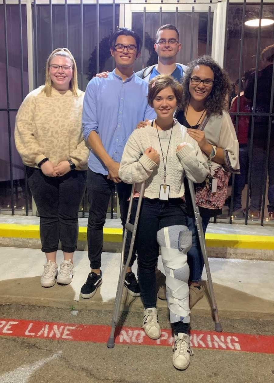 woman on crutches with leg brace with friends