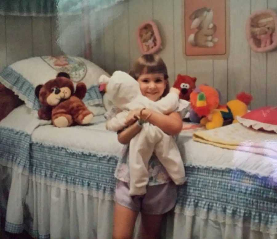 little girl with one arm holding a stuffed animal