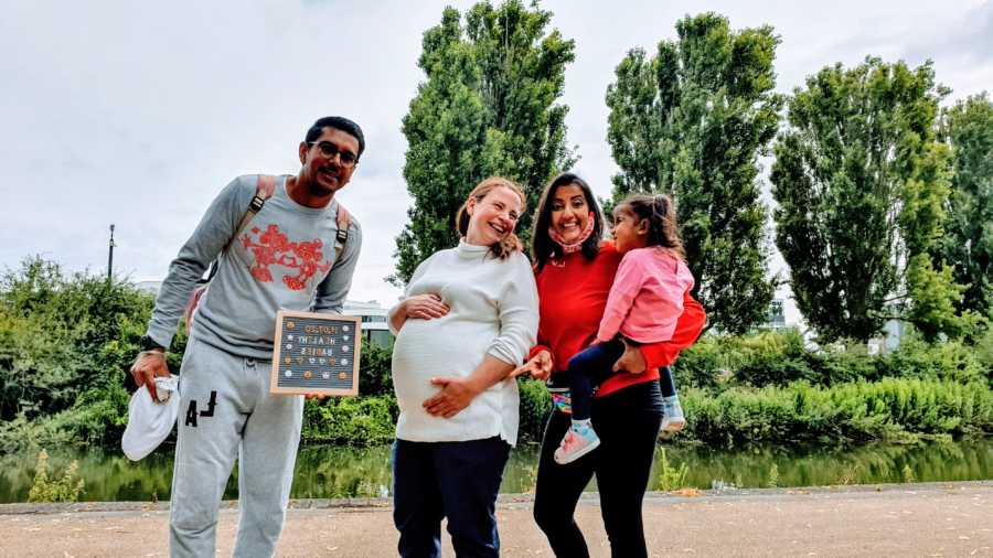 Family of three take photos with their surrogate as she carries their triplet boys