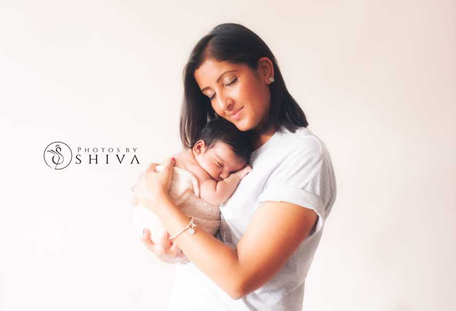Breast cancer survivor holds her newborn daughter conceived through embryo transfer surrogacy