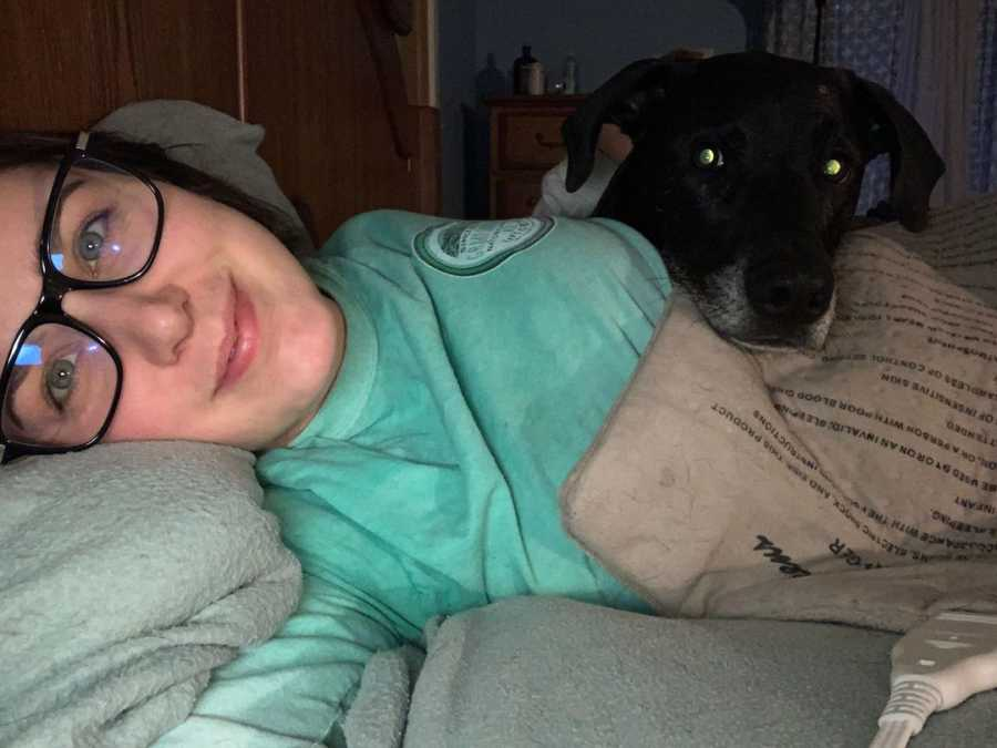 woman laying in bed with her dog