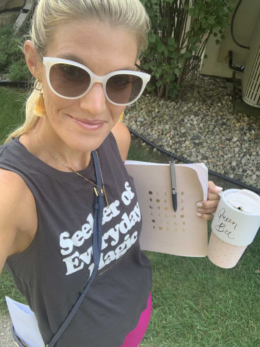A woman stands holding a planner and a coffee cup