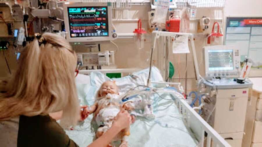 Little girl born with no immune system lays in the hospital bed before surgery