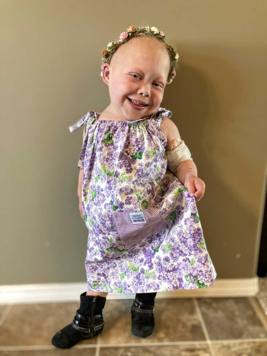 Medically complex little girl smiles and poses in a floral dress with a flower crown