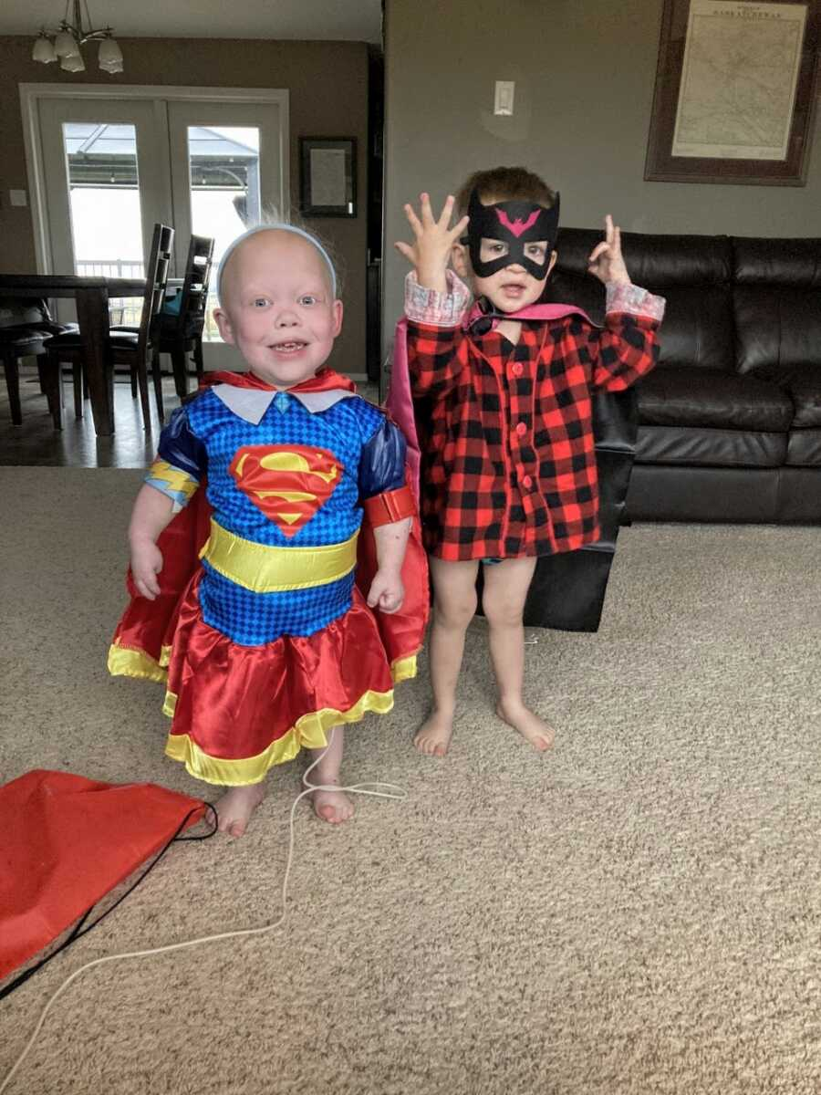 Little girl born with multiple rare conditions poses in a Superwoman costume next to her little brother