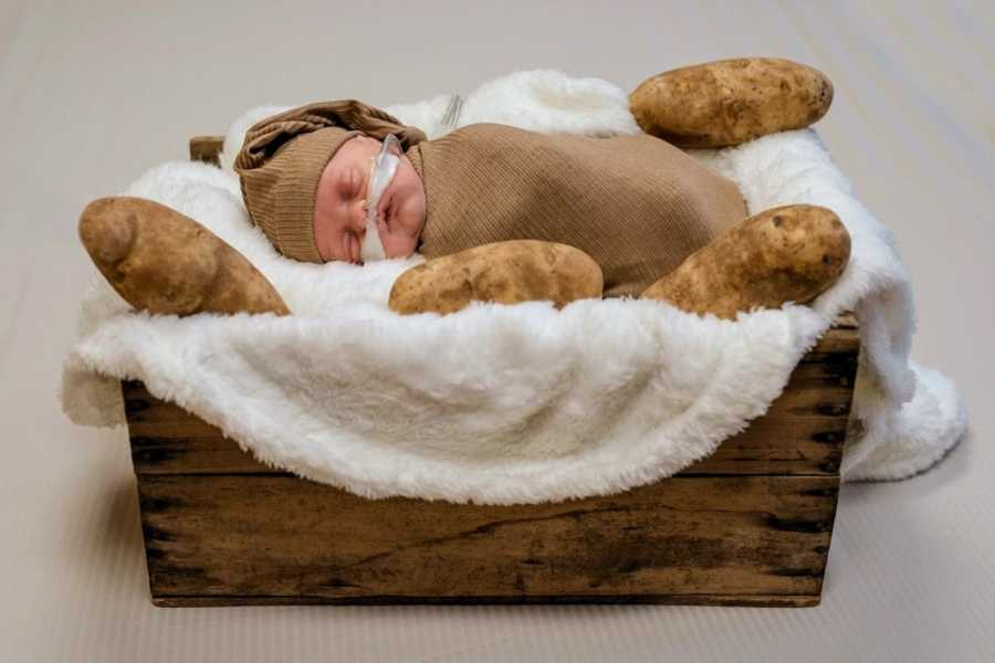 Mom takes newborn photos of firstborn son swaddled in a brown blanket with potatoes surrounding him in a basket