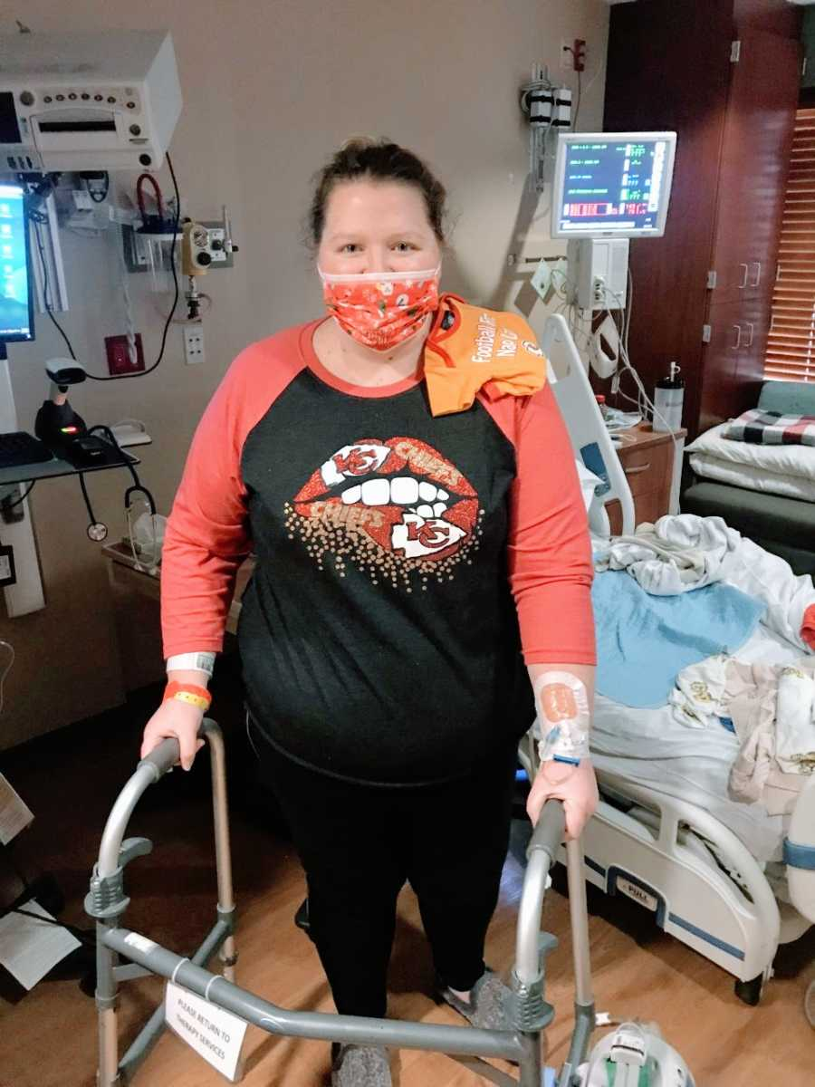Woman recovering from post-covid pneumonia and a traumatic birth takes a photo walking in the hospital with a walker