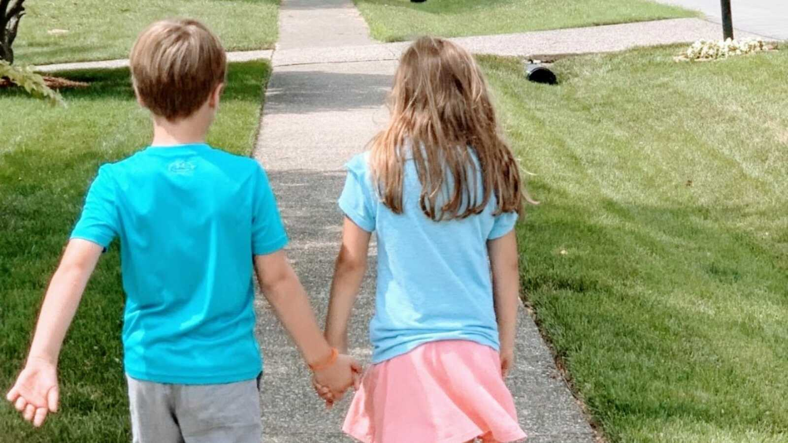 Foster mom takes photos of her kids walking hand-in-hand down the street in matching blue shirts