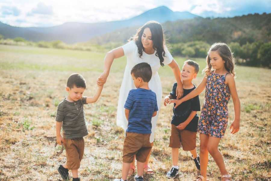 Single mom of 4 twirls her kids around while they dance during a family photoshoot