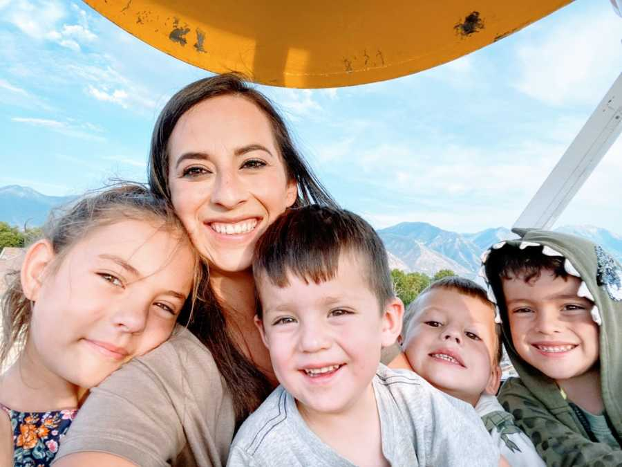 Single mom takes a selfie with her 4 kids while on a ferris wheel with mountains in the background