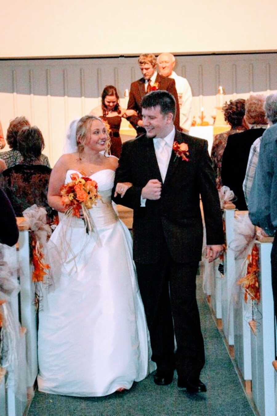 Young couple smile at each other while walking down the aisle at their wedding reception