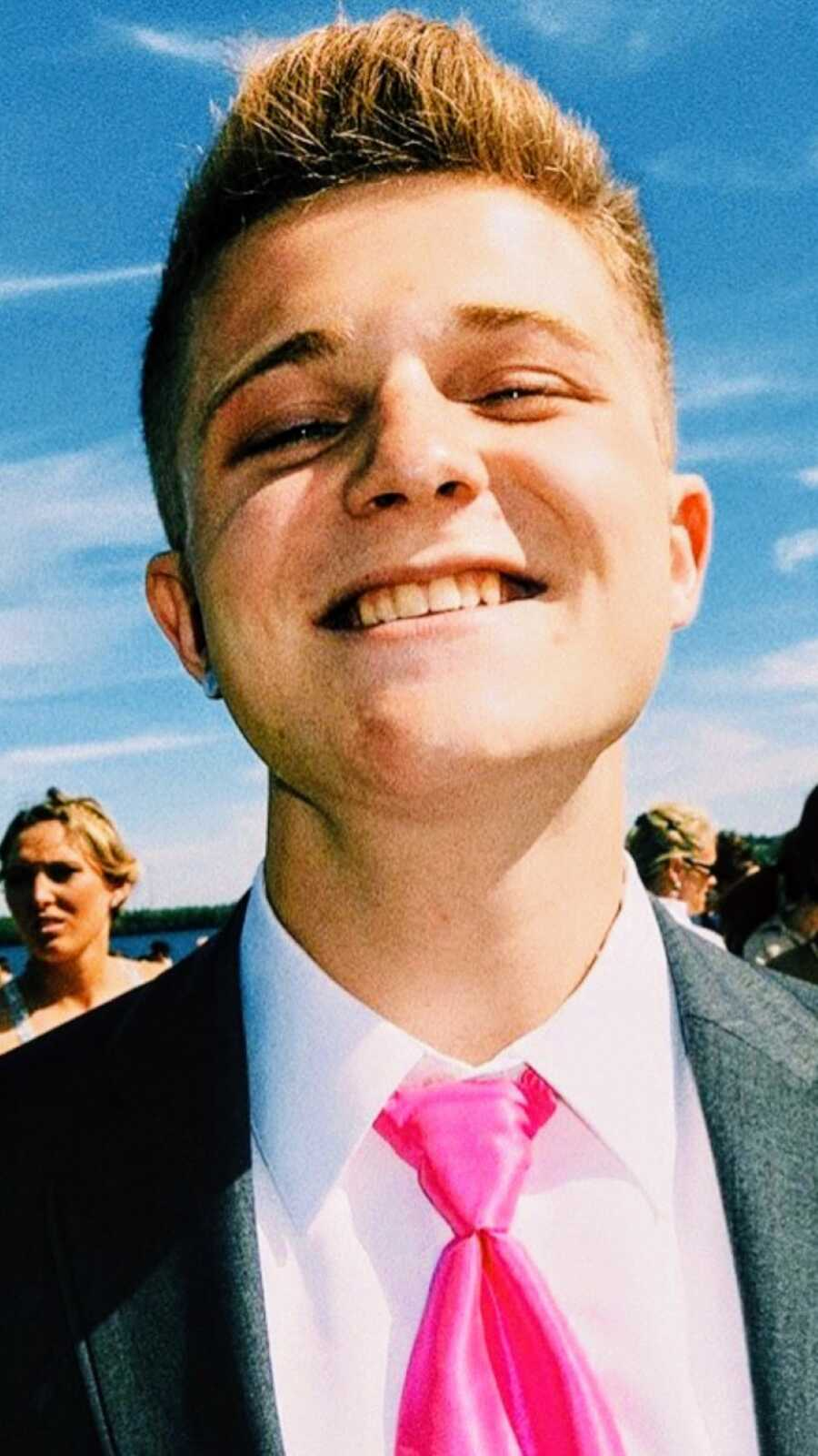Mom snaps an up-close photo of her son in high school while taking prom pictures in a suit and pink tie