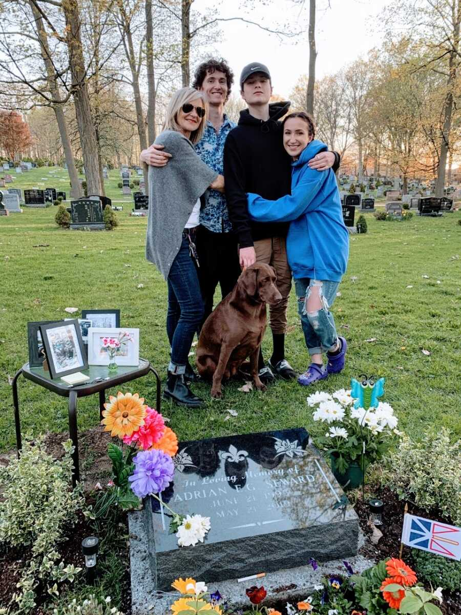 Mom hugs her three living children while standing in front of her oldest son's gravesite