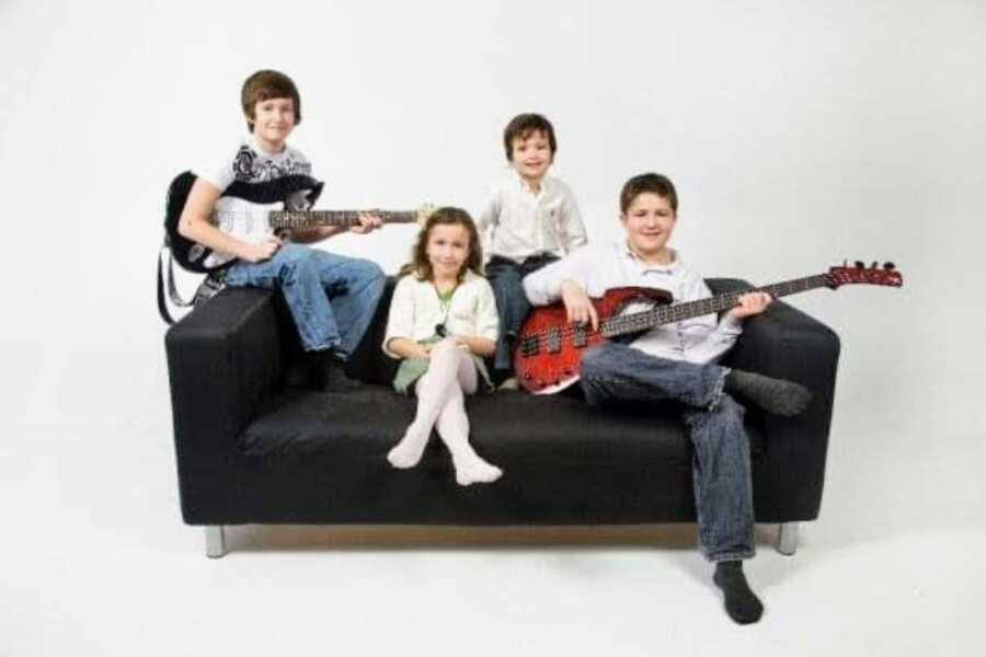 Mom of four takes photos of her three sons and one daughter sitting on a couch together, two sons holding electric guitars
