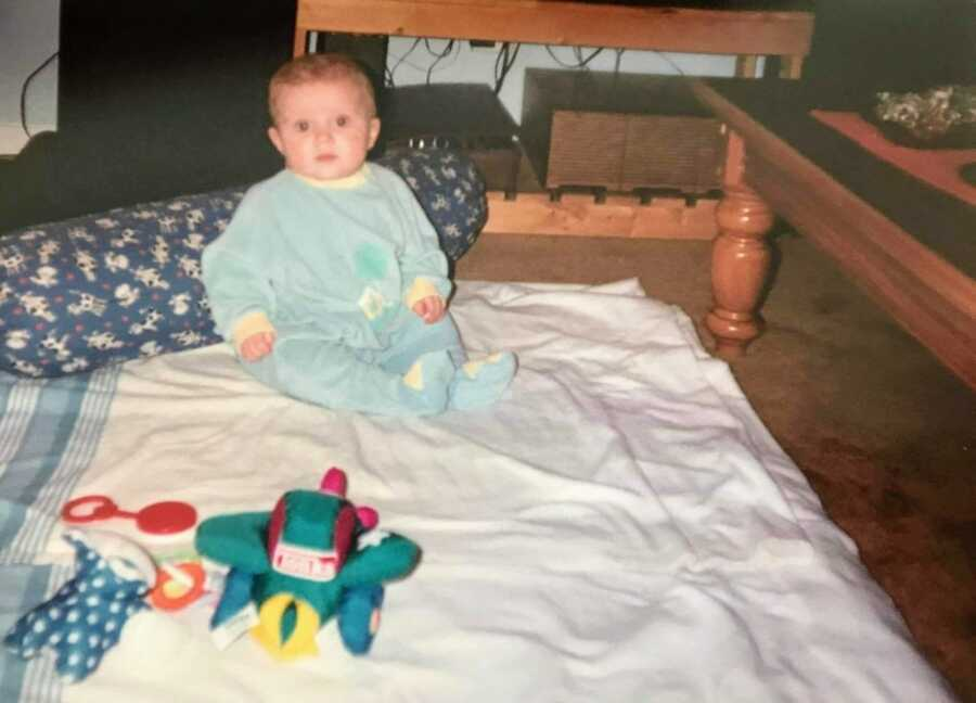 first-time mom snaps photo of her young son sitting up on a blanket on the floor in a blue onesie