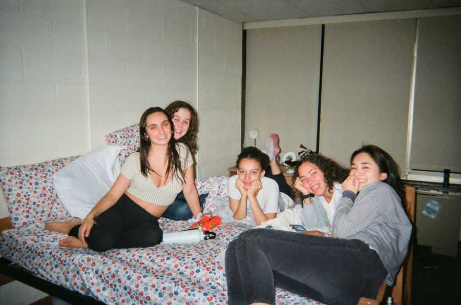 Five girls sit on a bed in a small room