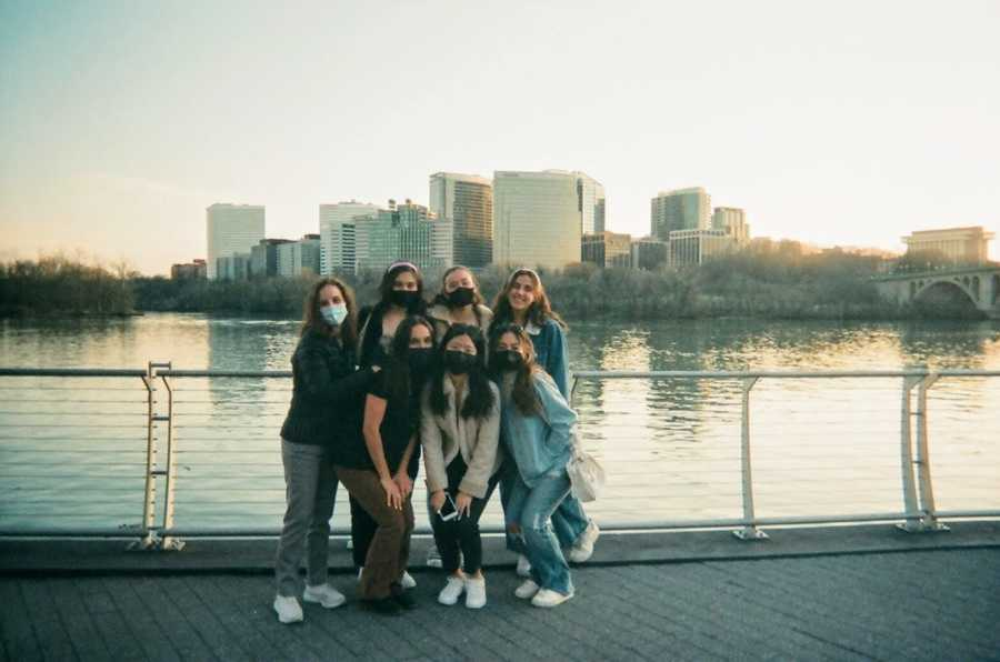 six girls staggered in front of river