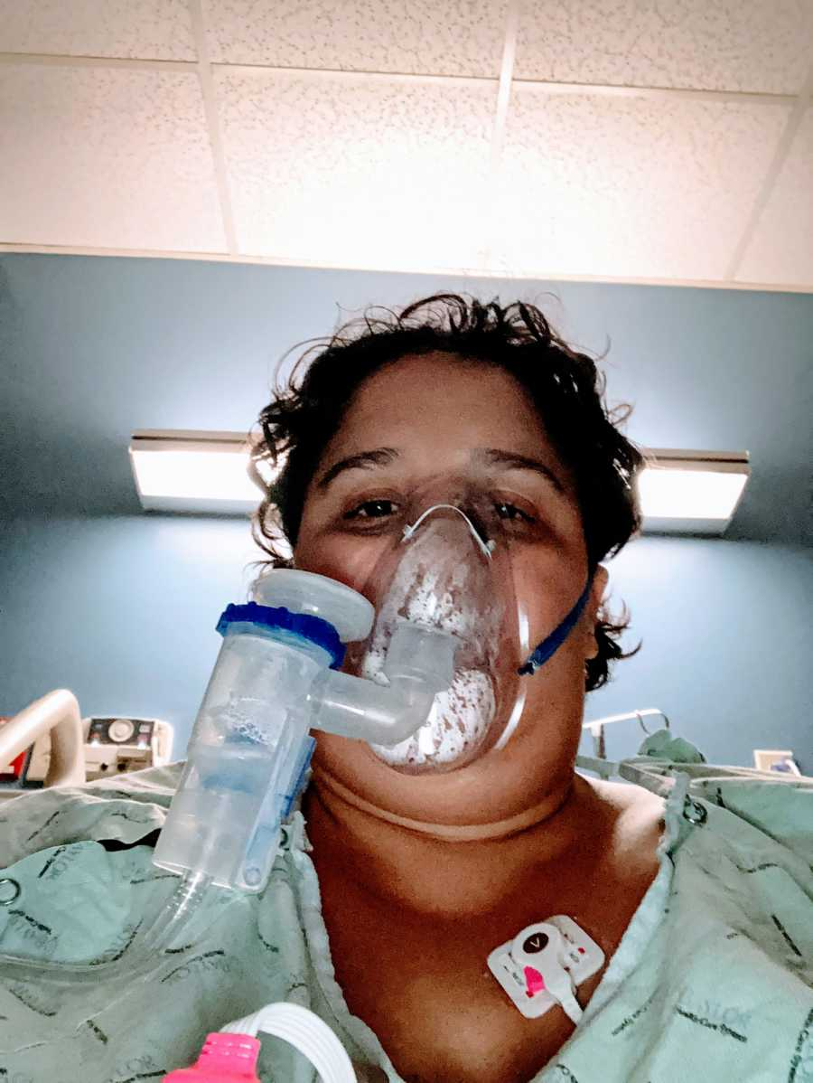Woman who contracted COVID-19 takes a selfie in a hospital bed while breathing through a breathing machine
