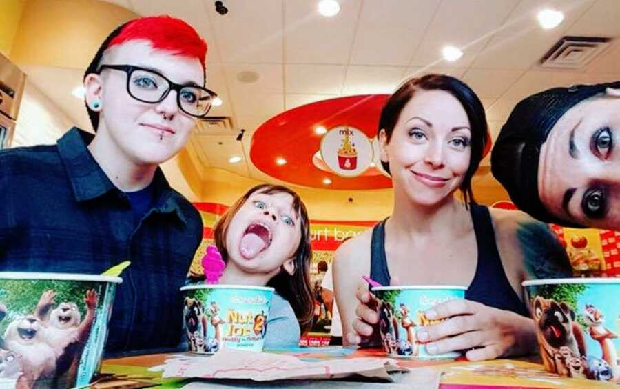 Autistic mom of 2 takes a selfie with her partner and her two children while they enjoy some fro-yo together