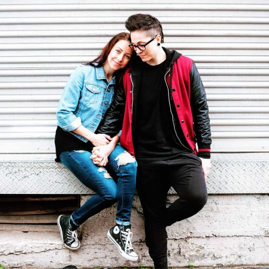 Queer couple take a photo together while holding hands, both wearing jackets and jeans