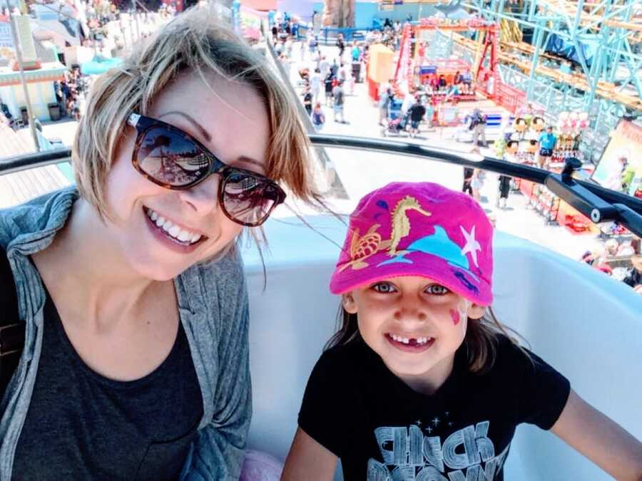 Autistic mother takes a selfie with her daughter while they ride a ferris wheel together at their local amusement park