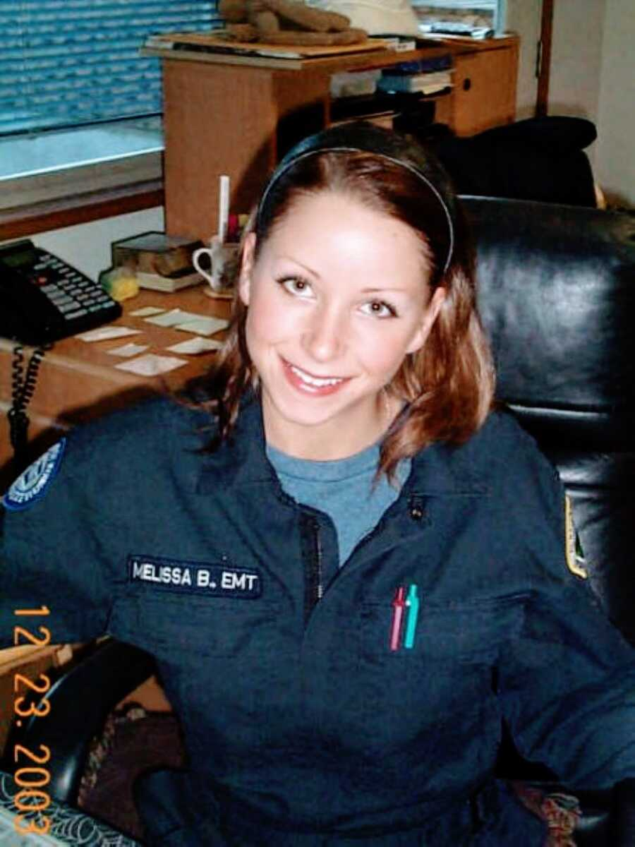 Young woman unknowingly battling autism smiles for a photo at her desk with her EMT uniform on