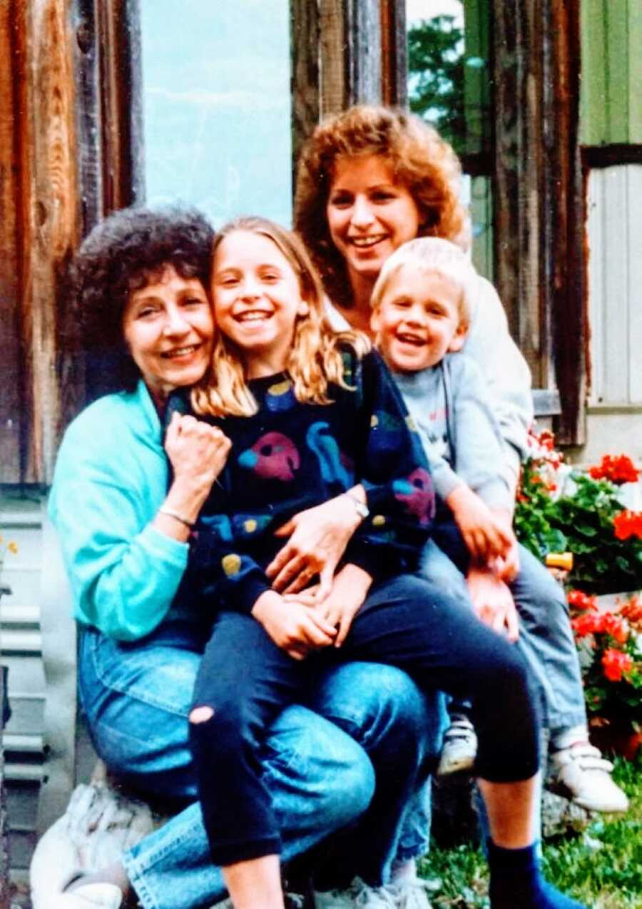Little girl in an 80's sweater smiles big for a family photo with her little brother, mom, and grandma