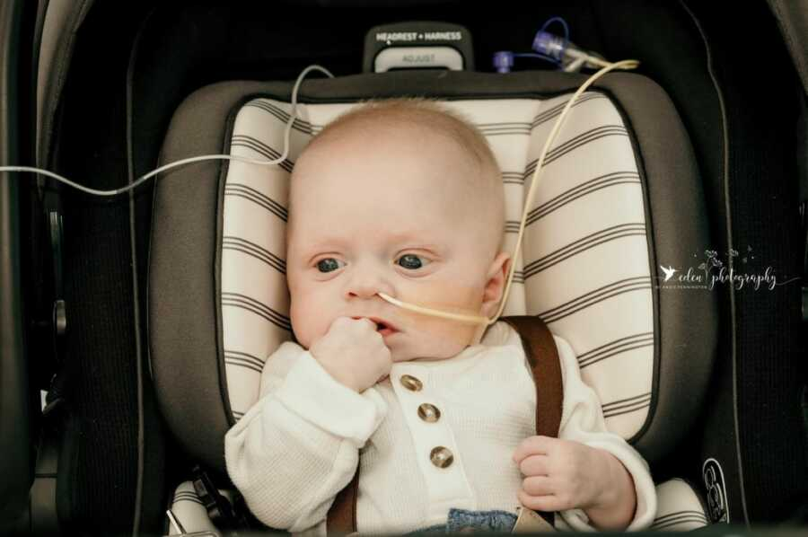 Little boy with rare Trichohepatoenteric syndrome sits in a car seat while attached to oxygen tube