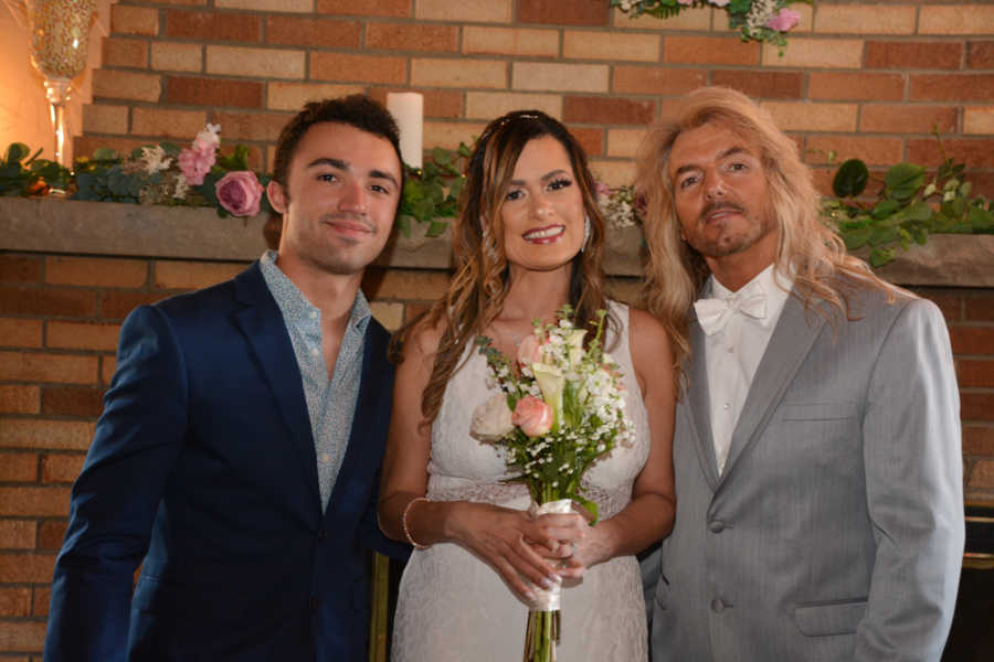 couple with bride's son on their wedding day