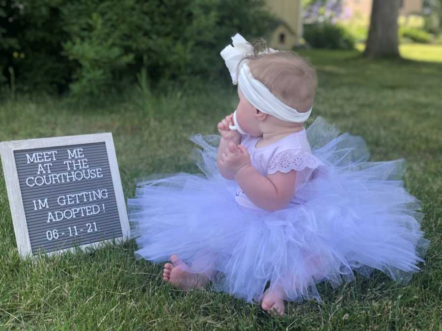 """Little girl wears a headband and a tutu while looking at a sign that reads """"Meet me at the courthouse, I'm getting adopted!"""""""