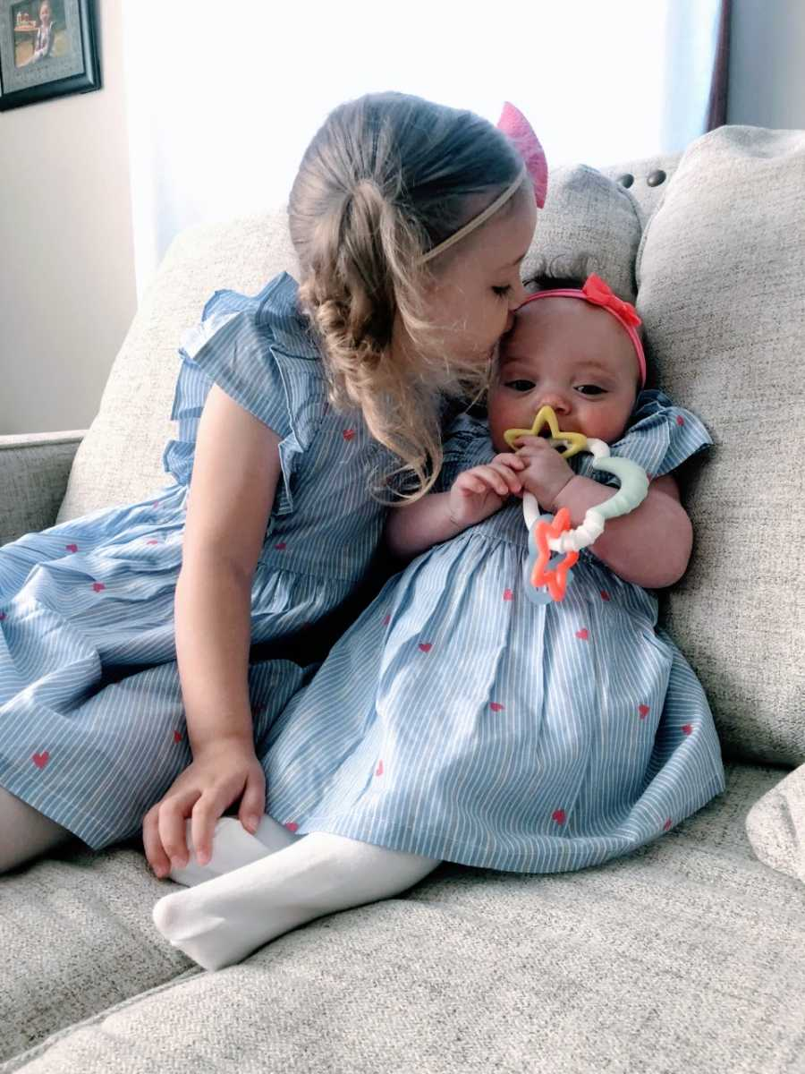 Siblings adopted out of foster care wear matching dresses while they sit on the couch together