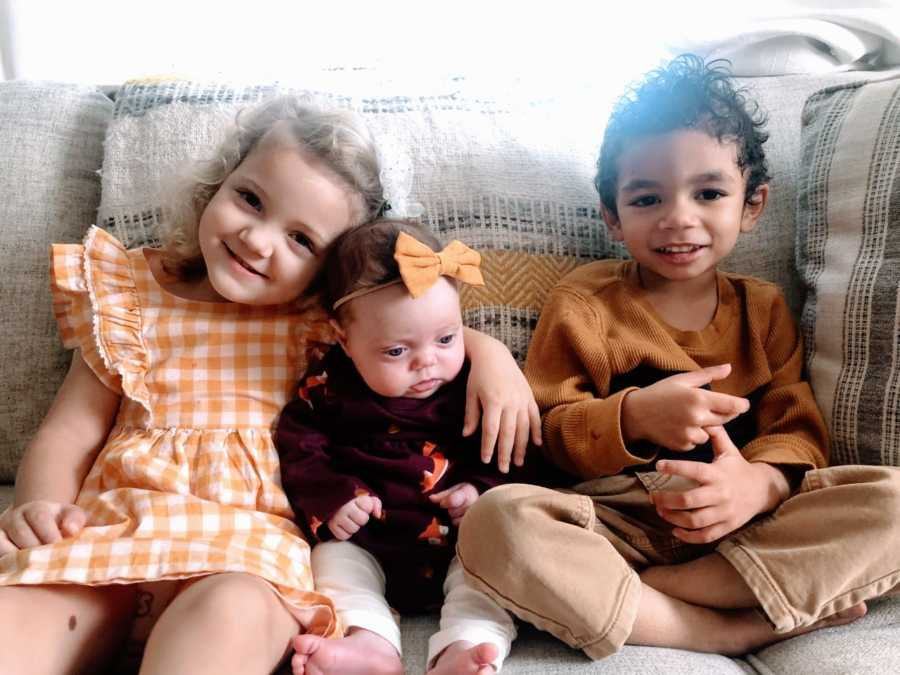 Little kids hug their newest sibling adopted out of foster care while sitting on a couch, all wearing fall colors