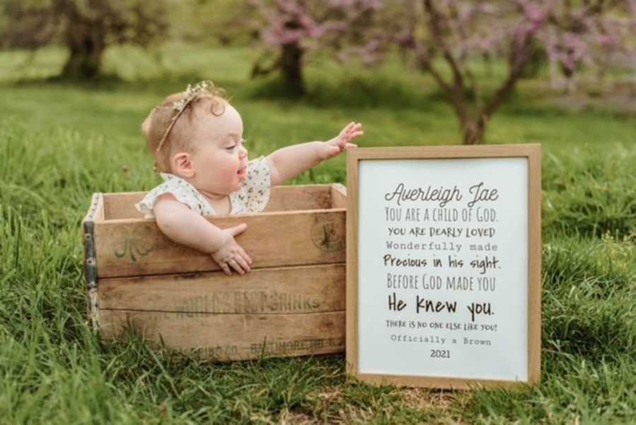 Little girl adopted out of foster care sits in a box with a sign next to her