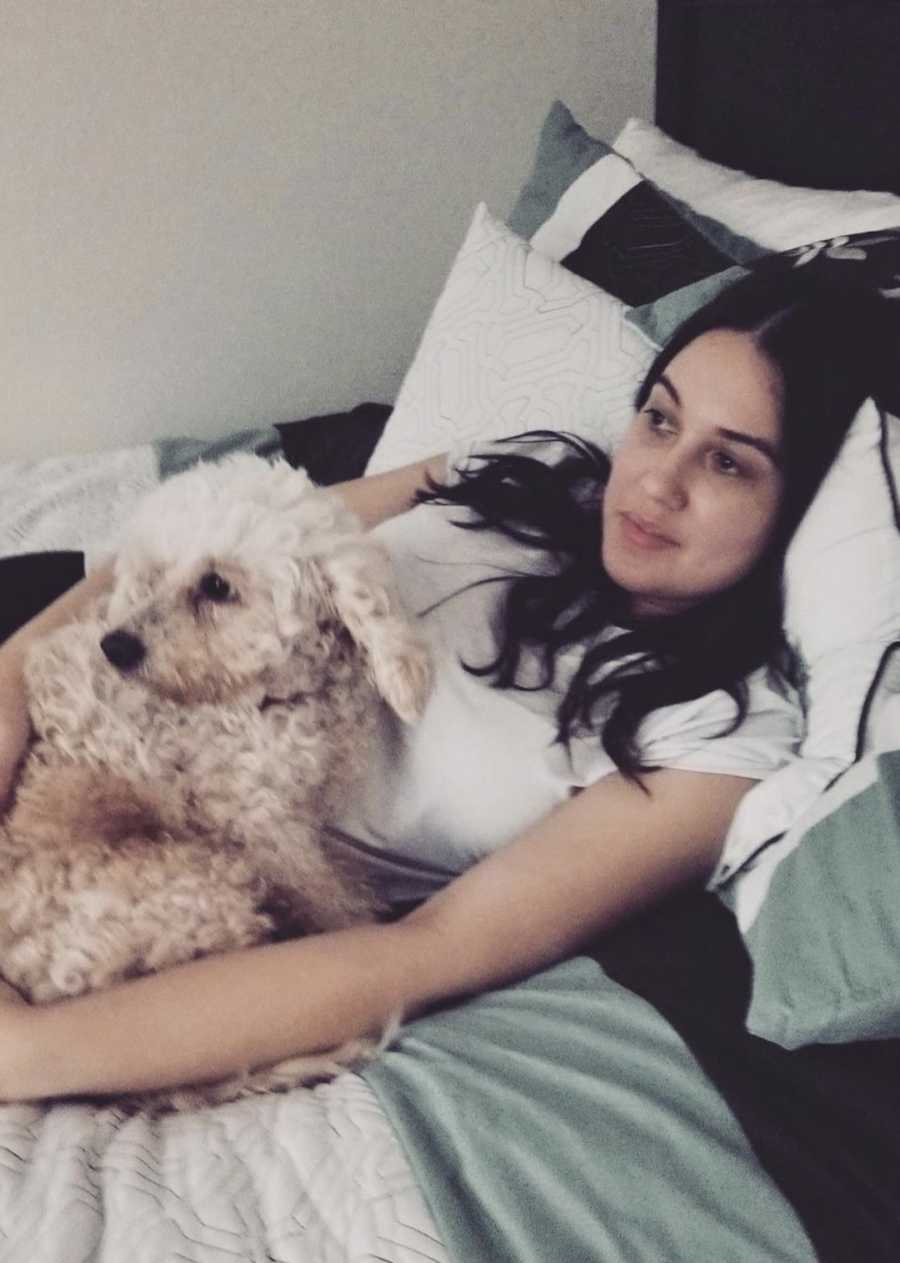 young woman in bed with her dog