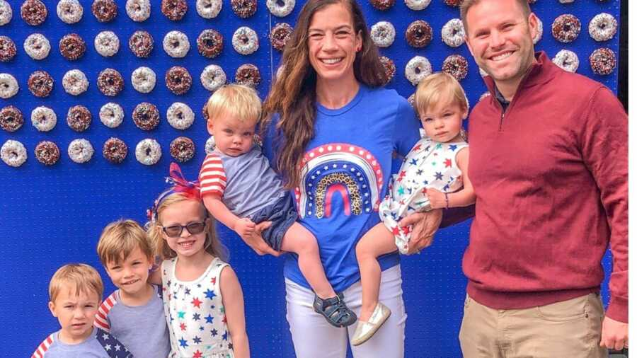 Family of seven dressed in red white and blue in front of donut display