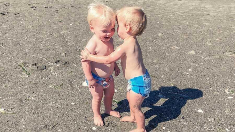 Twin boys hugging on sand at beach