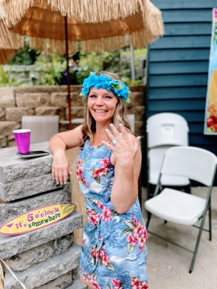 Woman smiles big and shows off her wedding ring at her Luau-themed surprised wedding