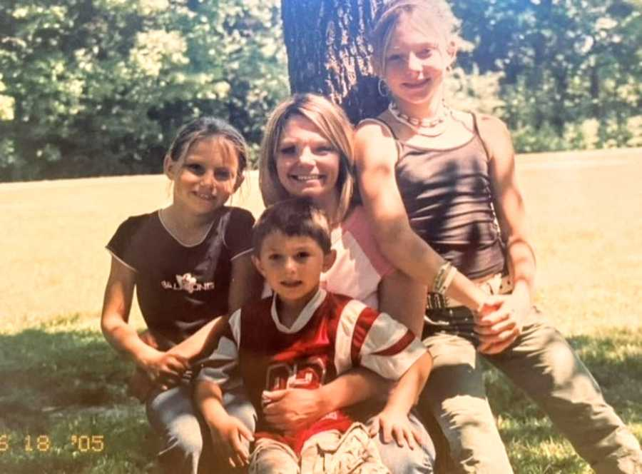 Young single mom of three takes a photo with her kids while they lean against a tree