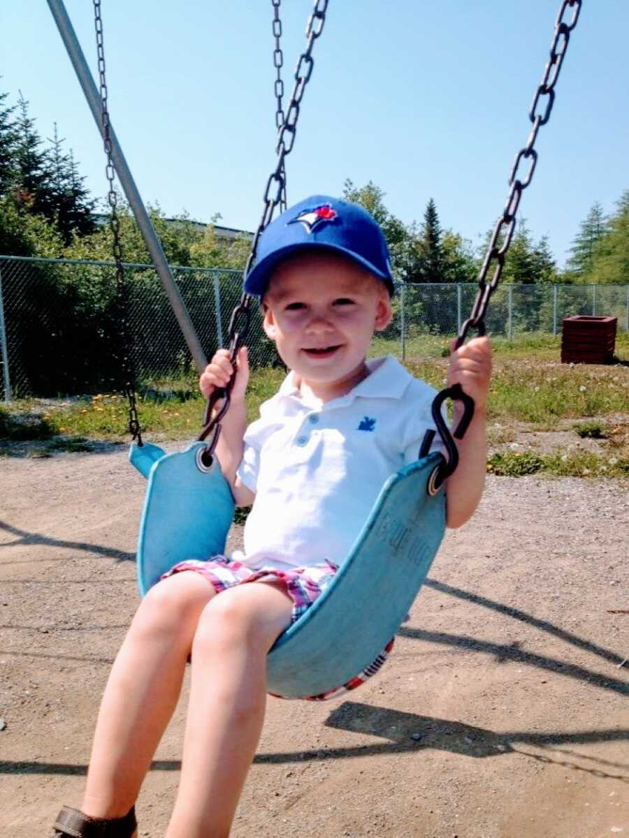 Young little boy in a white polo and blue hat smiles while swinging in his backyard